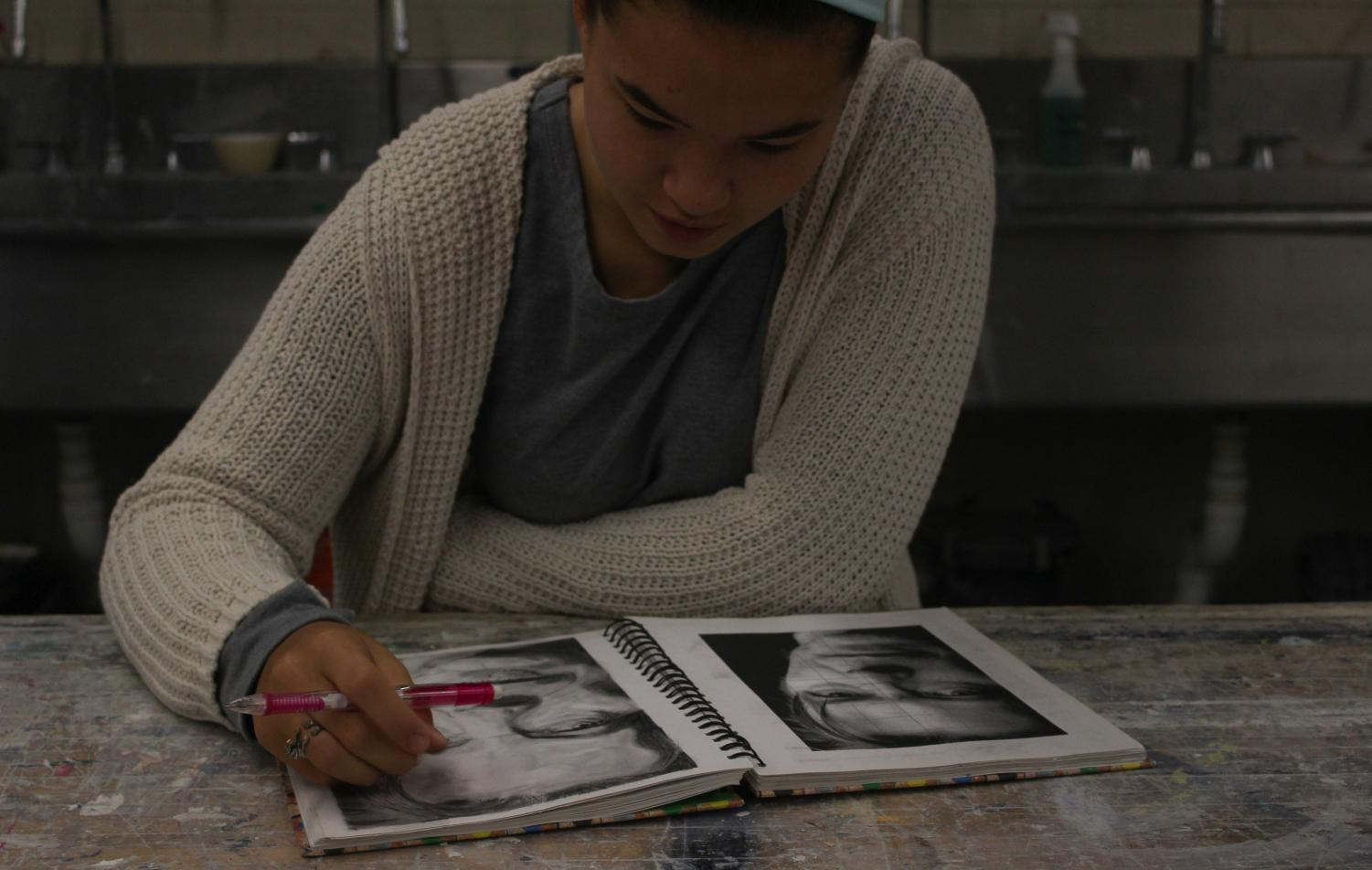 Stapel compares her portrait to a photograph of late artist David Bowie.